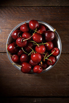 Overhead view of wet cherries in bowl on wooden table