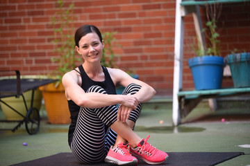 Portrait of smiling woman sitting on exercise mat against brick wall