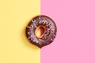 Overhead view of chocolate donut with sprinkles on colored background