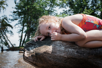 Portrait of wet girl in swimwear sucking thumb while lying on log against trees during sunny day