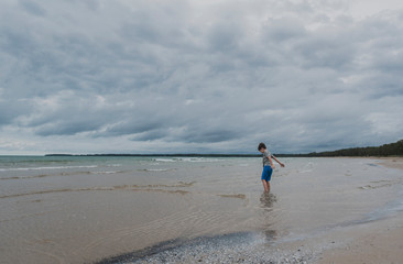 Side view of boy standing in sea against cloudy sky