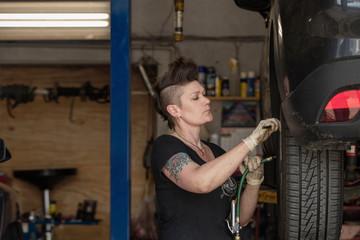 Hipster female mechanic repairing car's wheel in auto repair shop