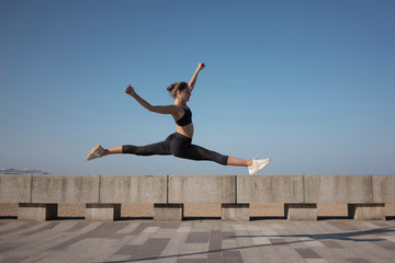Full length of flexible young woman with legs apart jumping on promenade against clear sky