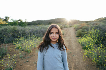 Portrait of girl standing on landscape against clear sky during sunset