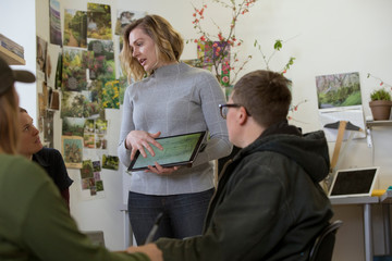 Businesswoman explaining to female coworkers over tablet computer while standing in workshop
