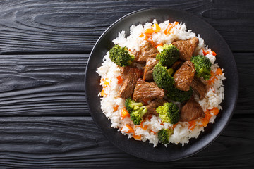 Portion of fried beef with broccoli with rice garnish and persimmon close-up on a plate. Horizontal top view