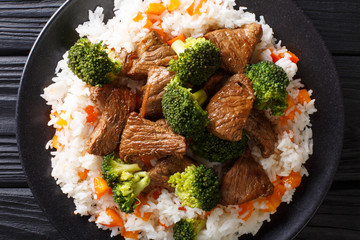 Asian beef with broccoli served with rice and persimmon close-up on a plate. horizontal top view