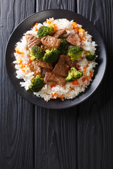 Portion of fried beef with broccoli with rice garnish and persimmon close-up on a plate. Vertical top view
