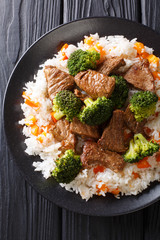Stir-fried beef broccoli with rice and persimmon side dish close-up on a plate. Vertical top view