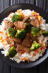 Asian beef with broccoli served with rice and persimmon close-up on a plate. Vertical top view