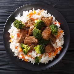 Roasted beef with broccoli with rice and persimmon side dish close-up on a plate. top view