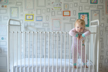 Portrait of cute baby girl leaning on railing while standing in crib against wall at home