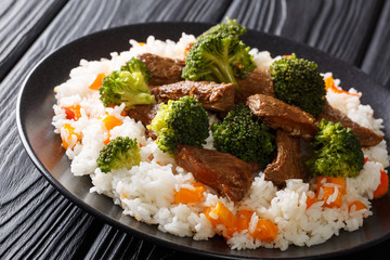 Delicious grilled beef with broccoli served with rice and persimmon close-up on a plate. horizontal