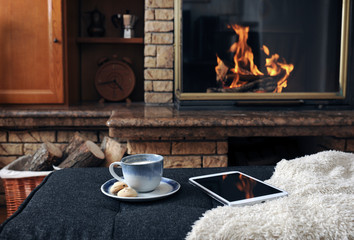 Tablet computer with food and drink on ottoman against fireplace at home