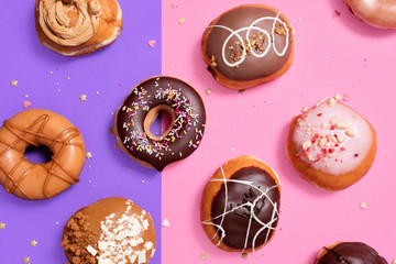 Overhead view of various donuts arranged on colored background