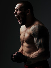 Shirtless angry young man screaming while standing against black background