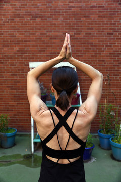 Rear view of woman with arms raised exercising against brick wall