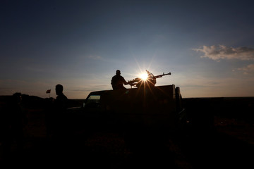 A PMF fighter rides in a military vehicle during his duty at Iraqi-Syrian border in Al-Qaim, the Iraqi town near Syria's Albu Kamal