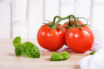 Ripe tomatoes with basil leaves in the wood background