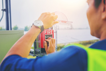 Electrical technician hands open and pushing fire alarm switch at solar panel plant.