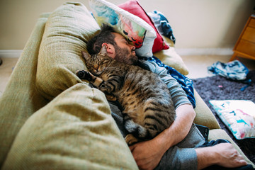 High angle view of man with cat sleeping on sofa at home