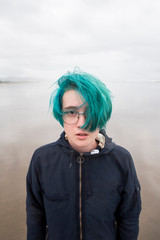 Portrait of teenage girl with green hair standing at beach against cloudy sky