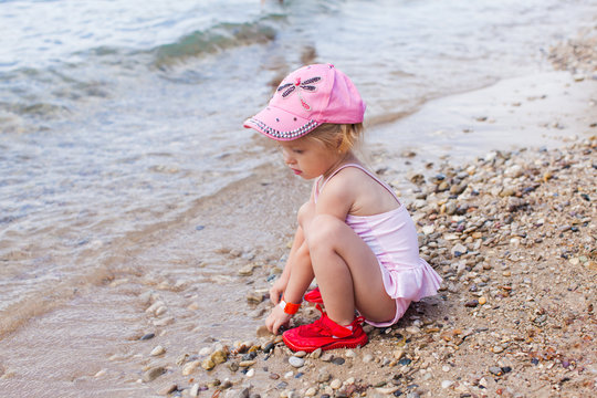 Pretty girl playing with sand on the seaside