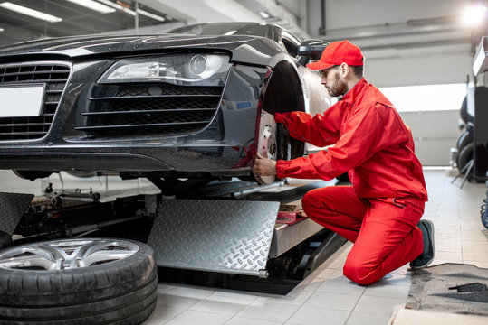 Auto mechanic in red uniform servicing sports car checking front brakes in the car service
