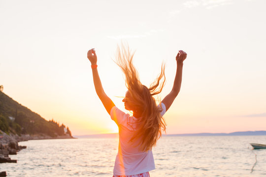 A beautyful woman feeling free meeting sun near the sea