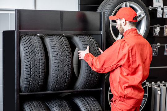 Car service worker in red uniform taking new wheel from the shelves of the wheel store