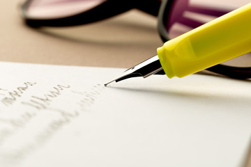 yellow fountain pen writing a letter, glasses behind