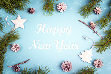 New year greeting message with fir branches and white decorations on the blue background.