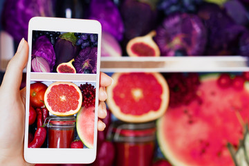 Vegan vegetarian woman female taking picture of healthy antioxidant colorful food, veggies, raw juice and fruits for eating in fridge: grapefruit, tomatoes, watermelon, fig and onion by smartphone