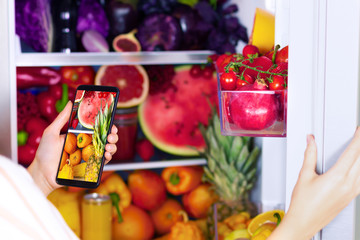 Vegan vegetarian woman female taking picture of healthy antioxidant colorful veggies, raw juice and fruits for eating after market in fridge: grapefruit, tomatoes, watermelon, pineapple by smartphone