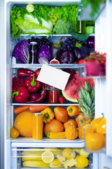 Fresh organic healthy raw antioxidant violet, red, green, orange and yellow food, vegetables, fruits and juices in vegan vegetarian opened full fridge of vitamins with space for text. Healthy eating.