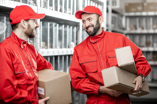 Two handsome warehouse workers in red uniform standing with boxes in the storage with auto parts or other products