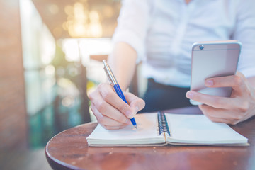Woman hand writing on a notepad with a pen and using a mobile phone in the office