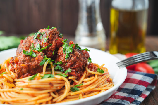 Spaghetti and meatballs with tomato sauce in white dish on wooden rustic board, Italian food closeup and top view.