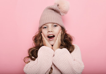 little girl child wearing pink winter hat and sweater over pink background, close up