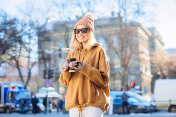 Blond positive hipster stylish finn woman in beige hat and hoody, warm mittens drinks coffee from disposable cup in winter time outdoor.