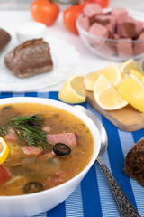 Traditional Russian soup Solyanka cooked with meat, sausages, salted cucumbers on wite bowl. Black bread, lemon, olived and tomatoes on color blue background, homemade food.