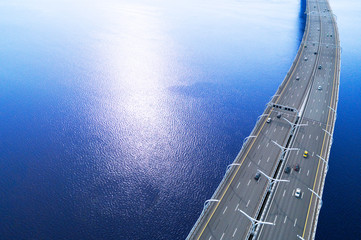 Aerial view of highway in the ocean. Cars crossing bridge interchange overpass. Highway interchange with traffic. Aerial bird's eye highway. Expressway. Road junction. Car passing. Bridge with traffic