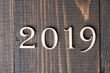 Carved wooden digits forming number 2019 on wooden background. New Year symbol, top view