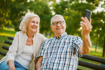 Happy senior couple is taking selfie in park.