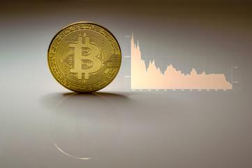 bitcoin coin on grey background - decreasing market price chart