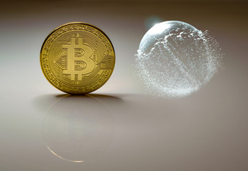 bitcoin coin on grey background - bursting soap bubble