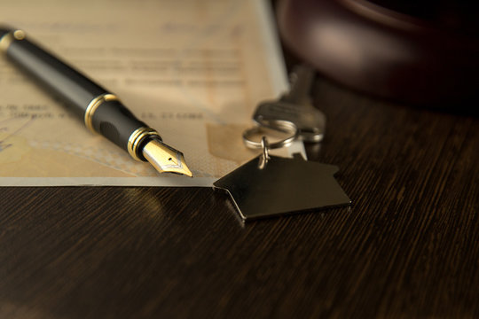 rental contract. A rental agreement / lease document with keys and pen.Keys on the signed contract of purchase and sale of the house and the handle