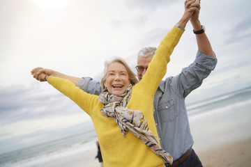 Lively senior couple playing around on beach together