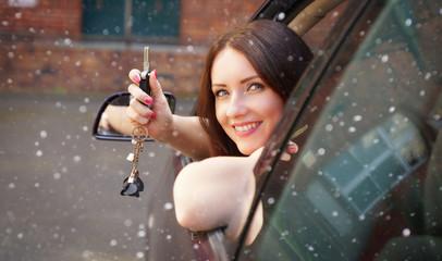 Frau hält Autoschlüssel aus dem Fenster im Winter