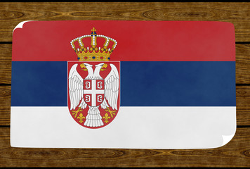 Illustration of a Serbian flag on the paper pasted on the woody wall